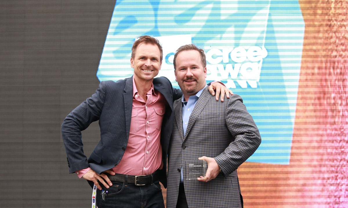 Two men posing with a Realscreen Awards trophy and their arms around each other